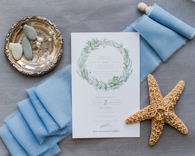 Beach inspired watercolor wedding invitation with succulents decorated with starfish and blue ribbon