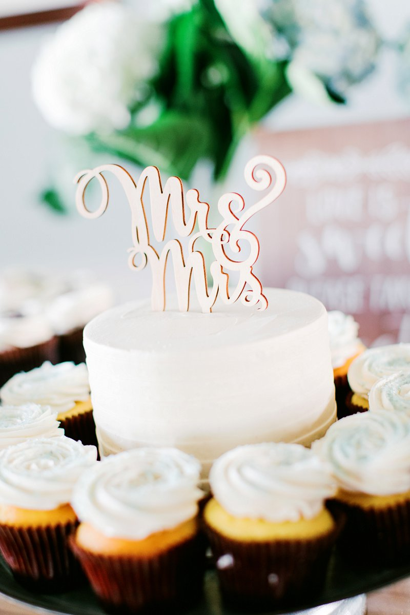 One layer wedding cake surrounded by cupcakes with wooden Mr and Mrs cake topper for beach house wedding