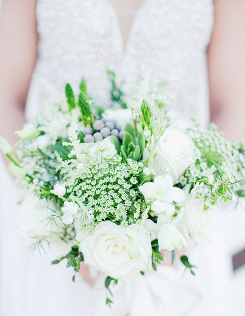 White and green bridal bouquet with dusty miller and succulents for blue beach wedding