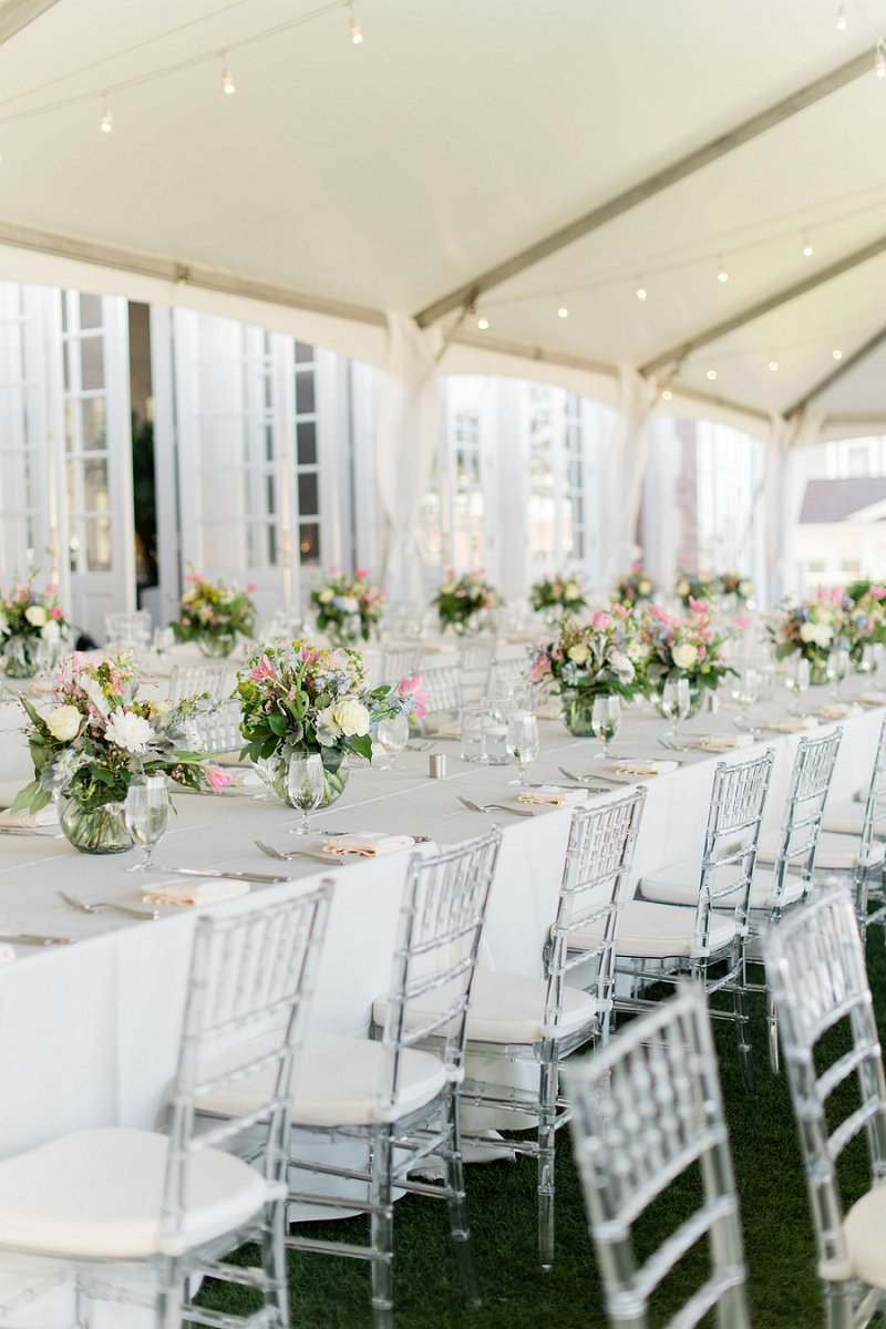 Outdoor tented wedding reception with long tables and ghost chairs and small low floral centerpieces