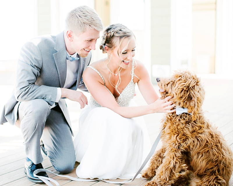 Bride and groom share a moment with their dog for their beach wedding in Virginia Beach