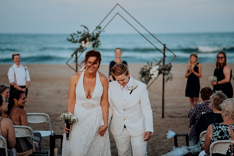 Two brides getting married in Virginia Beach at oceanside with a gorgeous handmade modern geometric ceremony arch