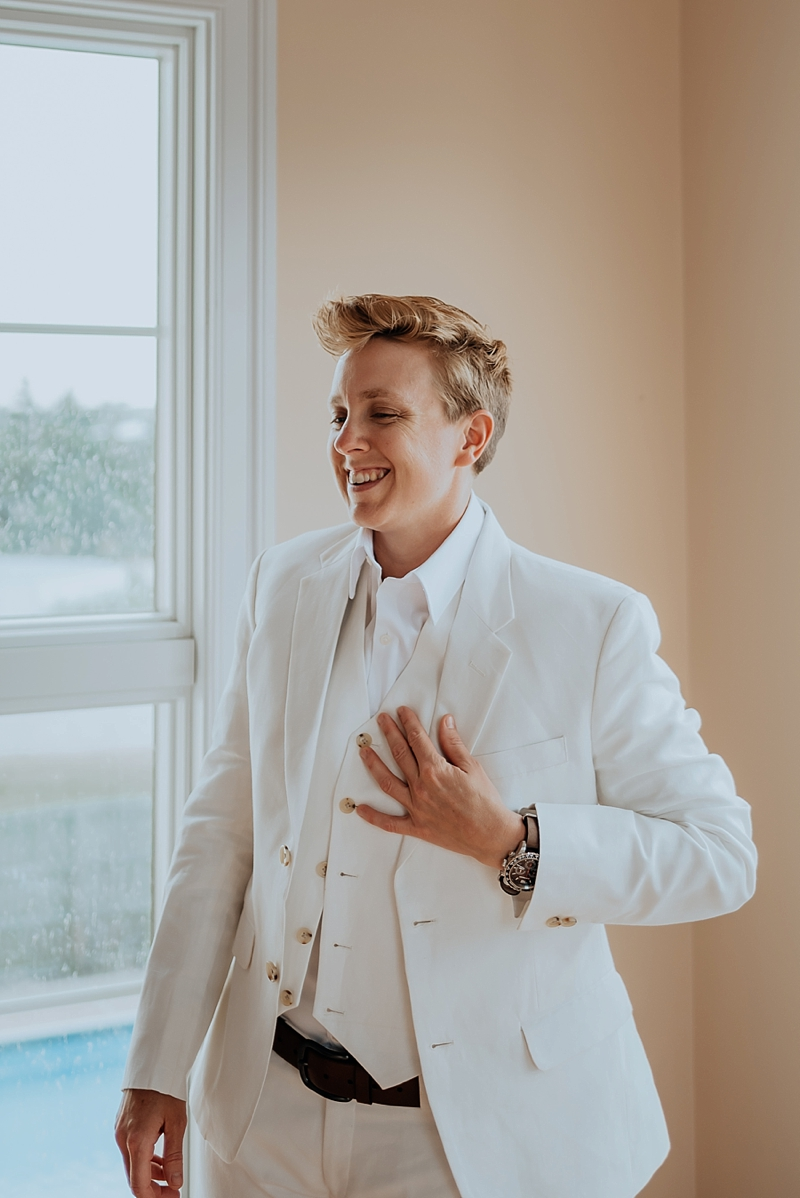 Dapper bride in her white wedding suit with white best and black belt for her lesbian wedding day