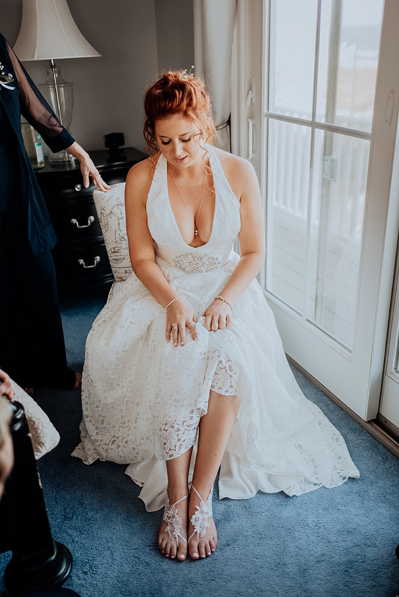 Lovely beach bride with a low v halter neckline lace wedding dress wearing barefoot sandals for her seaside wedding in Virginia Beach