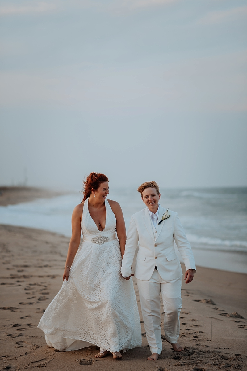 Beautiful moment between two brides walking on the beach on their wedding day in Virginia Beach