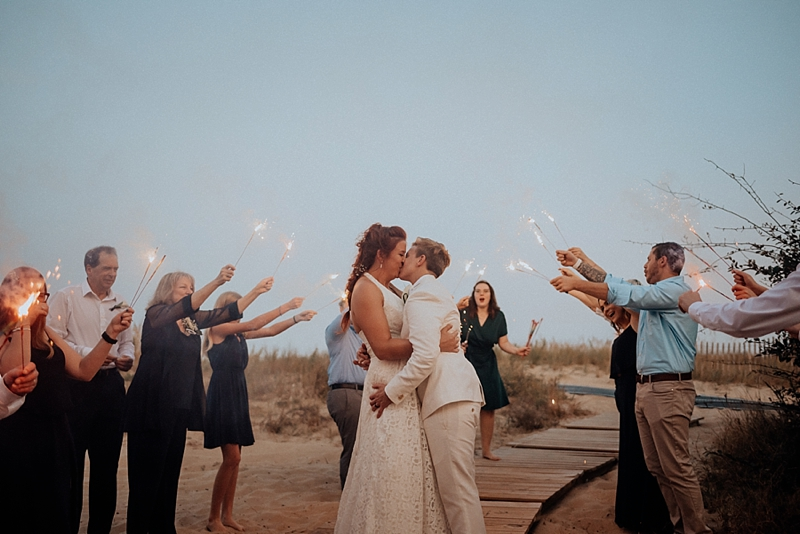Two brides being celebrated with a sparkler wedding exit on the beach in Virginia Beach