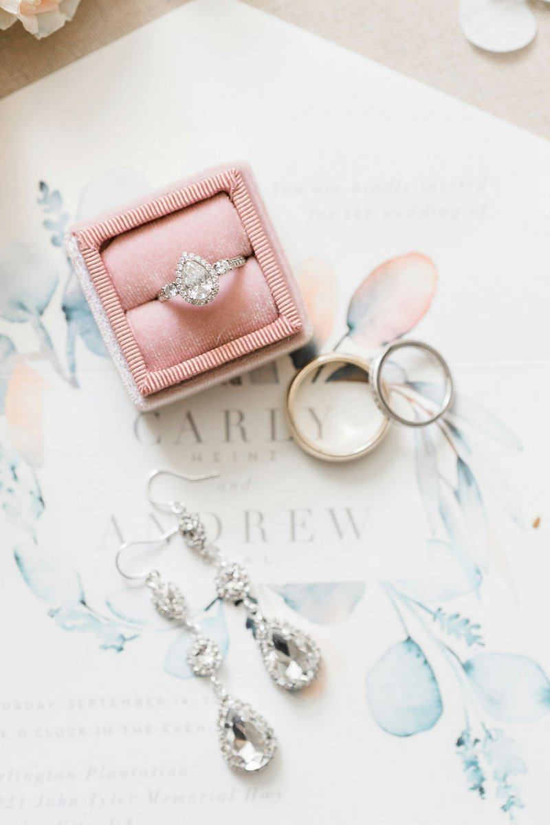 Teardrop shaped diamond solitaire wedding engagement ring with small embedded diamonds in the band nestled into a pink velvet ring box