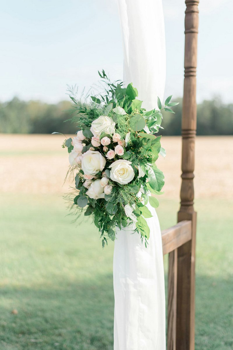 Chic rustic floral swag with spray roses and greenery for wedding ceremony arch drapery