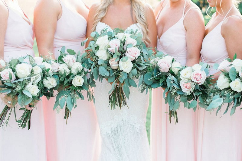 Classic rustic wedding bouquets with roses and eucalyptus for bridesmaids in pink dresses