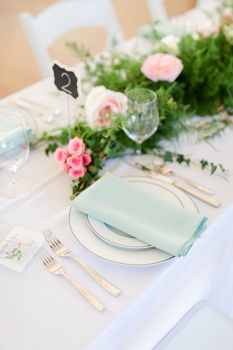 Simply classic wedding place setting with pastel mint green napkin and silver rimmed plates for a summer Williamsburg wedding at the Williamsburg Community Building
