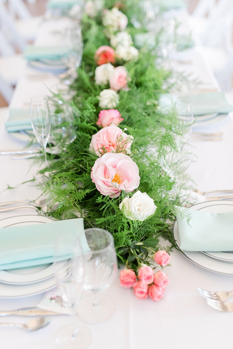 Long greenery garland with pink flowers for summer wedding centerpiece on white tablecloth in Williamsburg Virginia