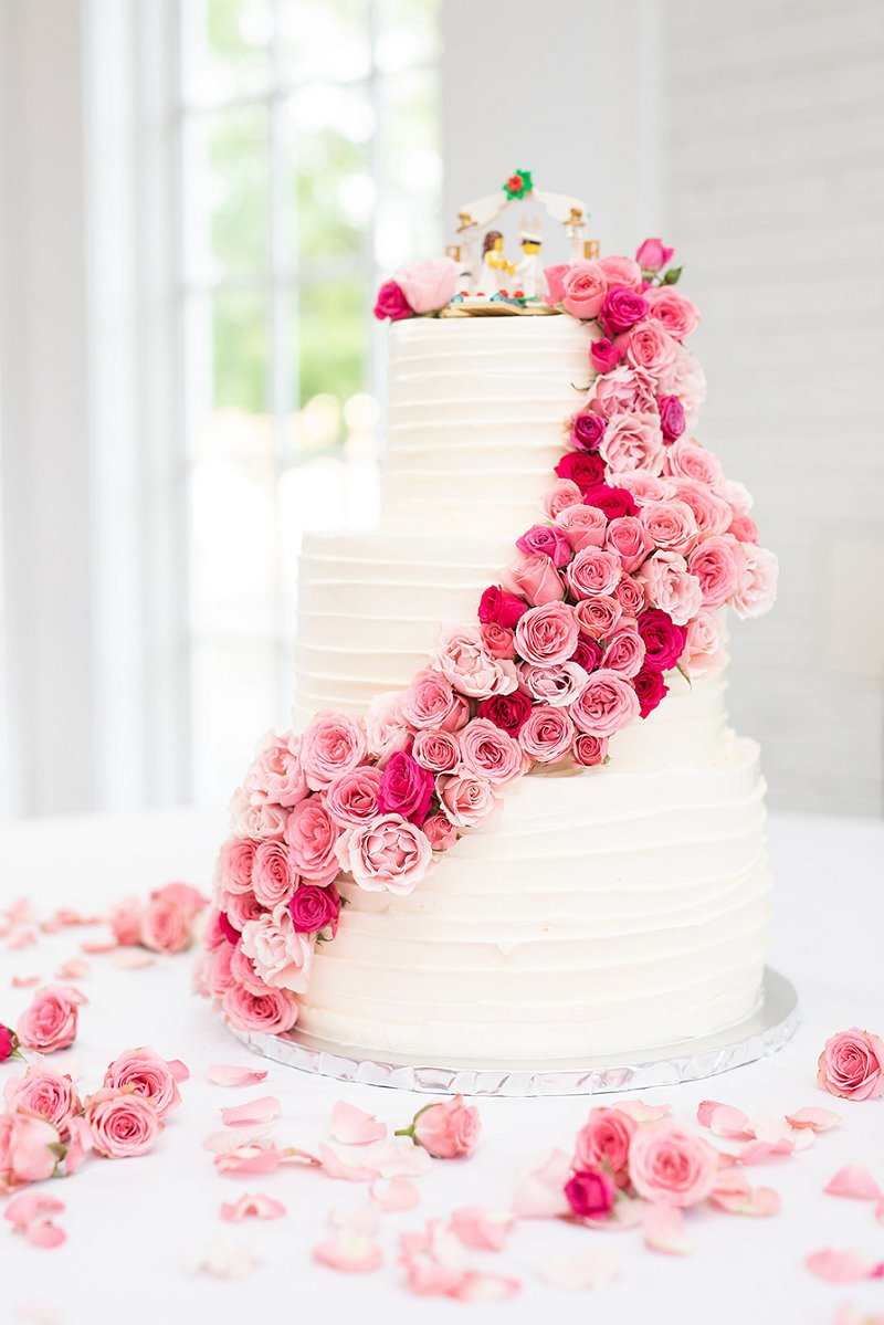 Three tiered white wedding cake with cascading ombre pink roses and adorable Lego wedding cake topper