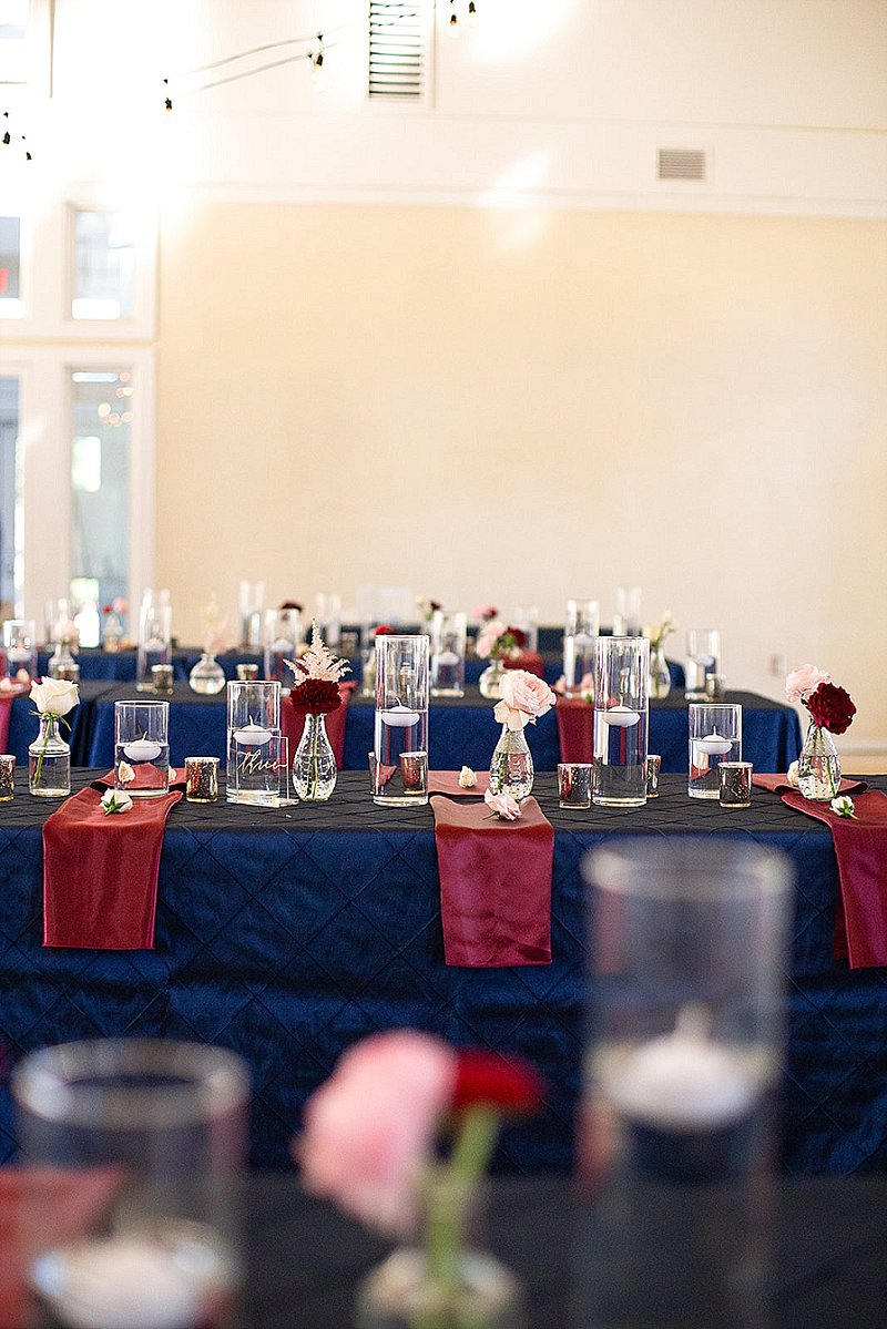 Navy blue tablecloths and burgundy red napkins on long tables for fall wedding reception decor