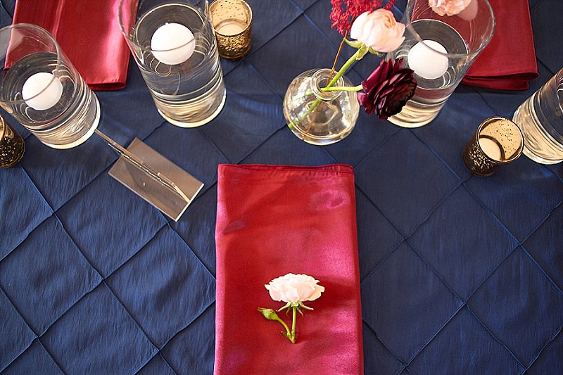 Quilted navy blue wedding tablecloth with red napkins for fall wedding reception decor