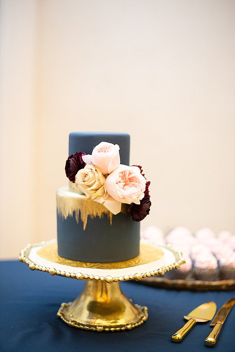Small two tiered navy blue wedding cake with painted gold swashes and florals for fall wedding