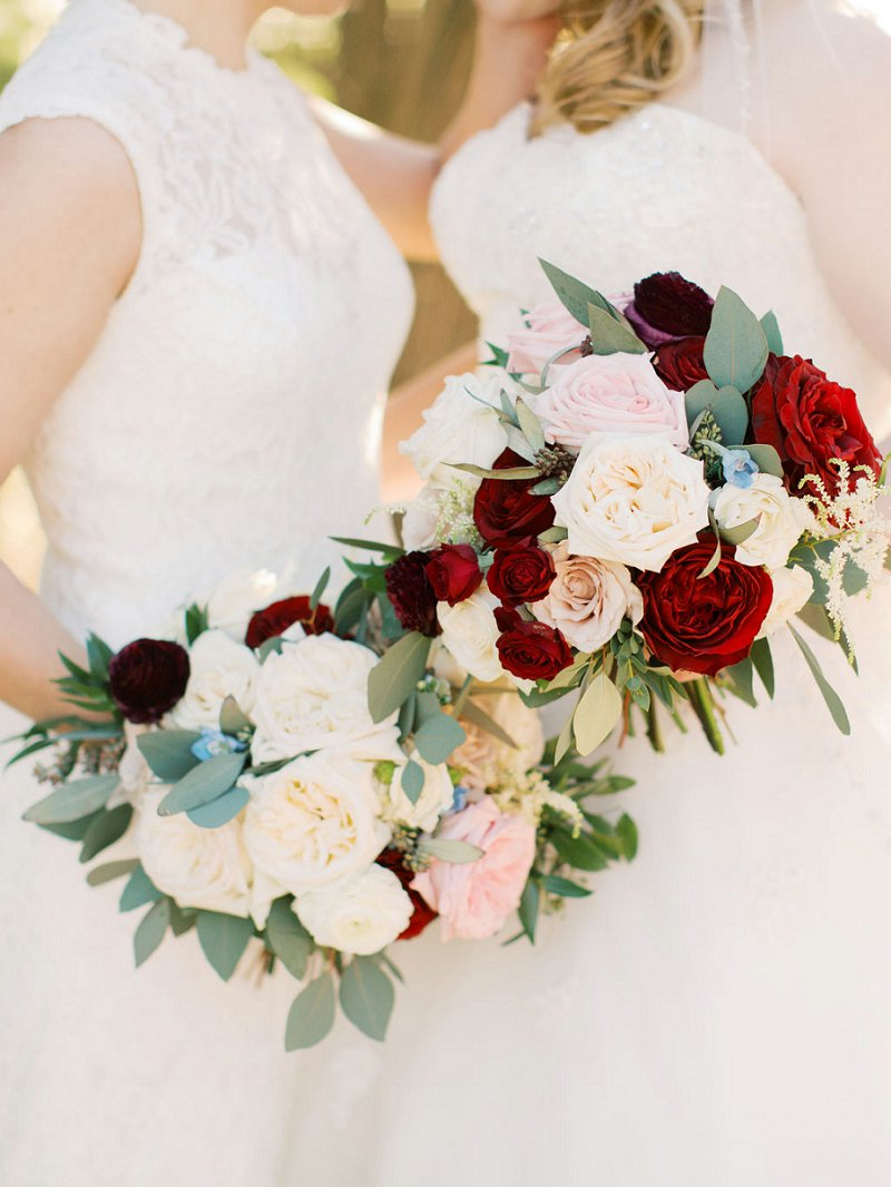 Red and pink bridal bouquets with unique roses and textured greenery for a rustic wedding