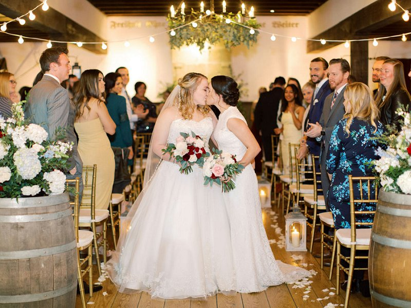 Romantic LGBTQ wedding at Williamsburg Winery in Virginia with two brides celebrating under bistro lights