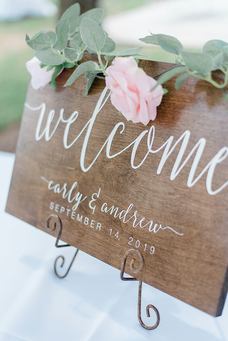 Wooden wedding welcome ceremony sign with white calligraphy and personalized date for rustic styled wedding