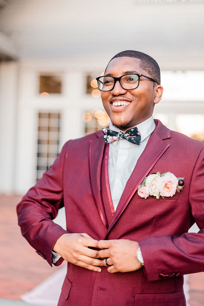 Handsome black groom in dapper burgundy red wedding suit with patterned floral bow tie and unique alternative pocket boutonniere