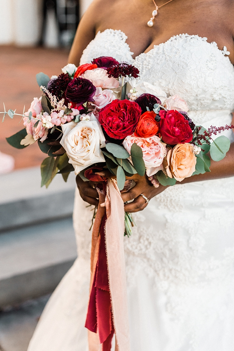 Red and pink wedding bouquet with ranunculus and garden roses for nontraditional fall bride in Virginia