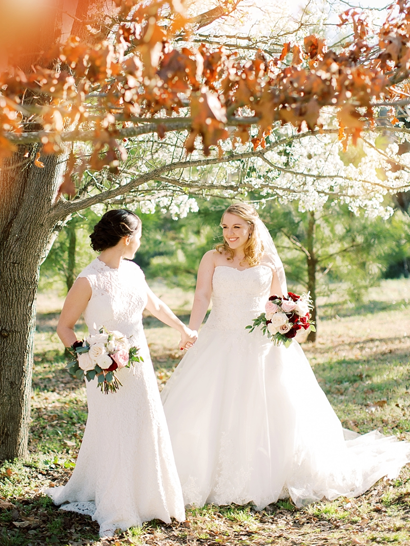 Romantic LGBTQ wedding day at Williamsburg Winery in Virginia with two brides in complementary lace bridal gowns