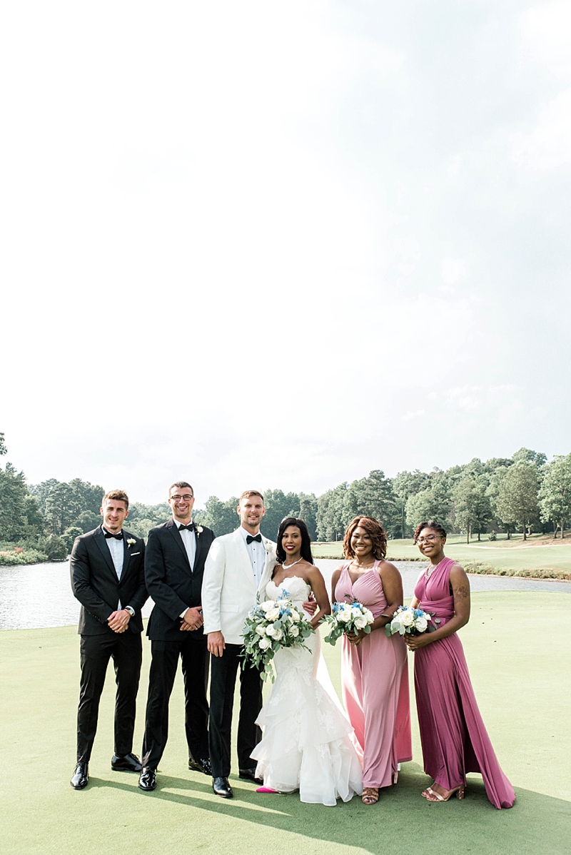 Beautiful wedding party dressed in tuxedos and pink bridesmaid dresses at Fords Colony Country Club in Williamsburg Virginia