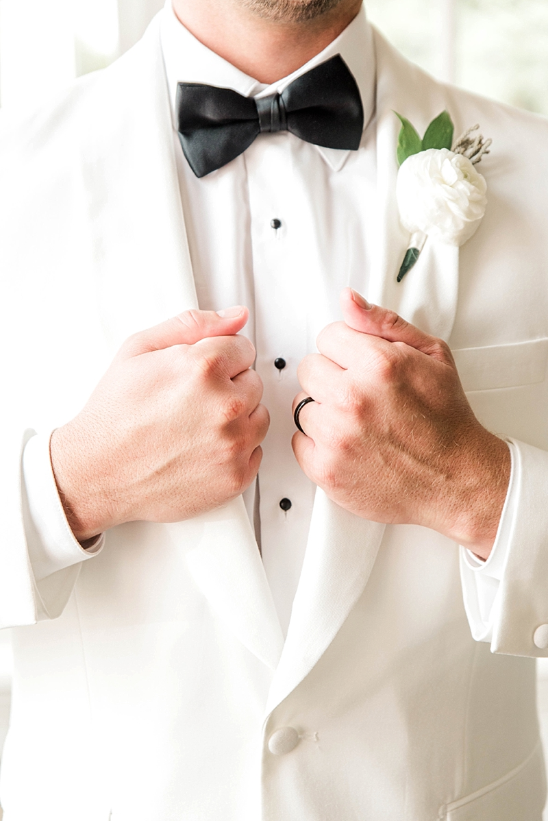Timeless white tuxedo jacket with black bow tie and white ranunculus boutonniere for classic groom style